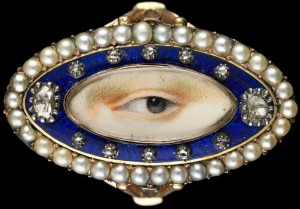 Rose gold oval ring surrounded by a blue enamel border containing ten small and two large diamonds enclosed in a border of natural split pearls. Brown left eye. Purchased from Edith Weber, New York. Dimensions: ¾ × 1 ¼ × ⅞ in.